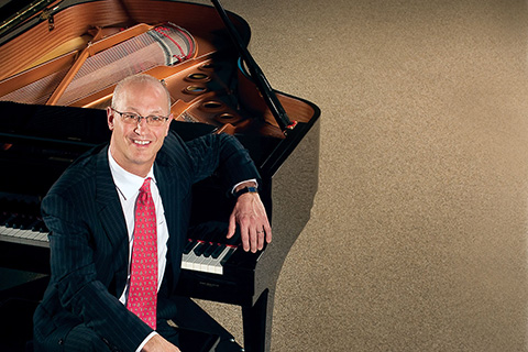 Dean Berg poses in a suit while sitting at a piano