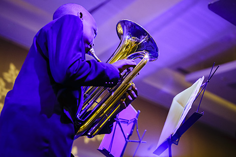 Youth artist performs with a brass instrument while wearing a suit.