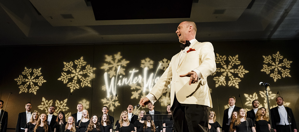 A man wearing a white suit directs a coral group at Winter Wonderful